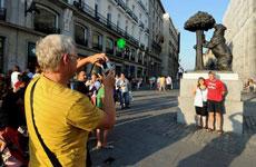 Turistas hacen fotos en la Puerta del Sol de Madrid. / A. Merino